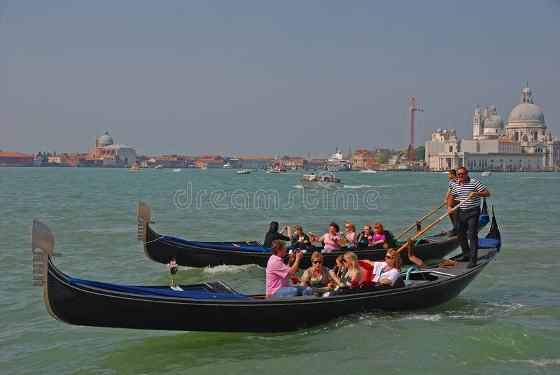 Gondolier rowing oar for tourist gondola in Venice gliding through the Venetian canal with them taking pictures & posing stock photo