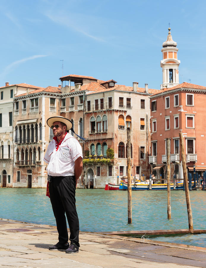 Gondolier standing on the pier. VENICE, ITALY - 26 JUNE, 2014: Gondolier standing on the pier. The profession of gondolier is controlled by a guild, which issues royalty free stock photos