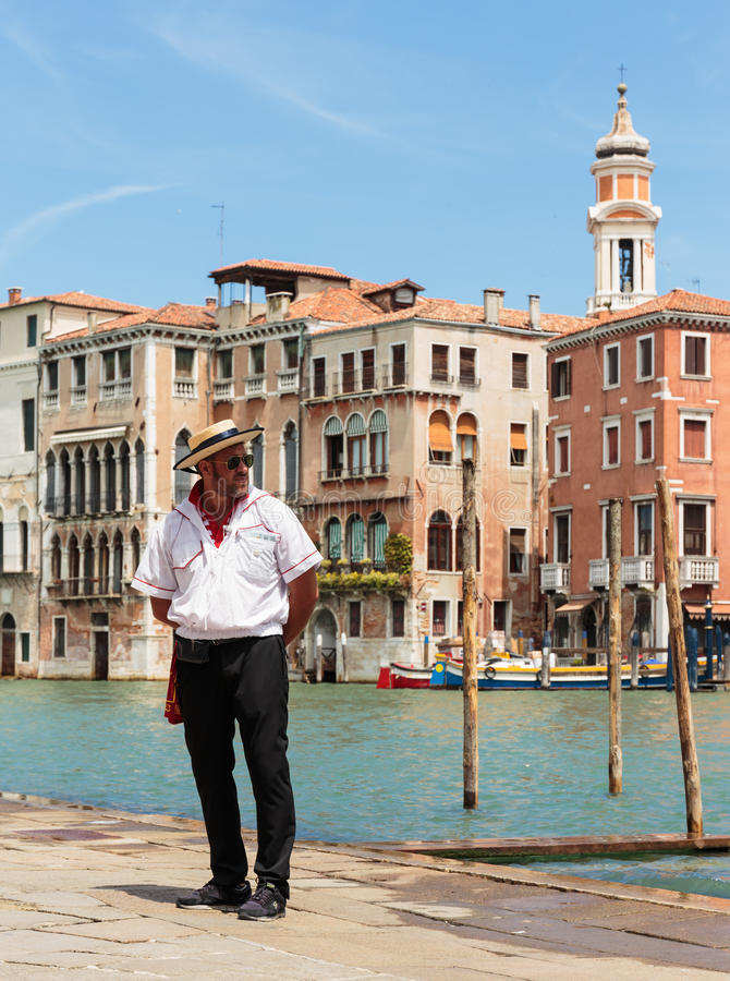 Gondolier standing on the pier. VENICE, ITALY - 26 JUNE, 2014: Gondolier standing on the pier. The profession of gondolier is controlled by a guild, which issues royalty free stock photography