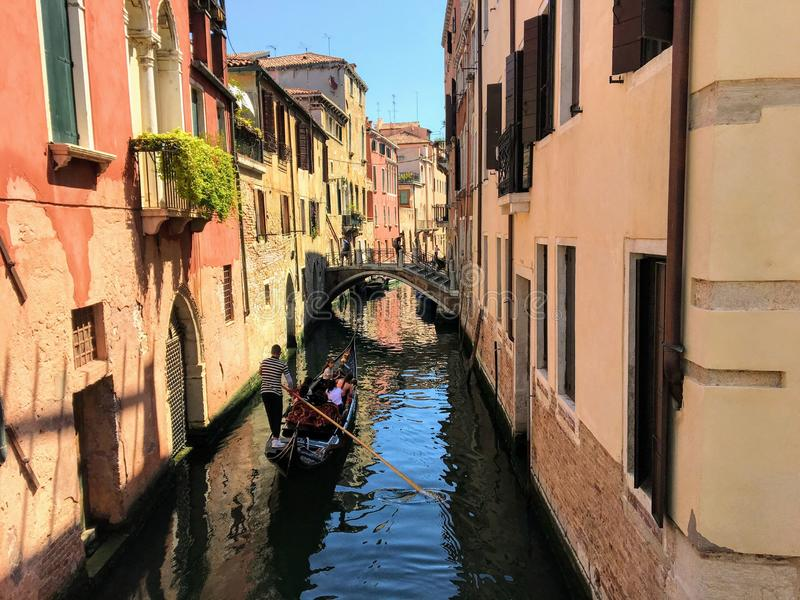 A gondolier takes his gondola full of tourists down a narrow small empty canal royalty free stock photos