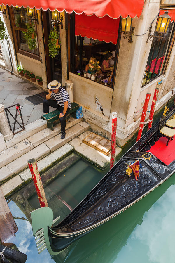 Gondolier in Venice at the pier. VENICE, ITALY - 26 JUNE, 2014: Gondolier on the pier. The profession of gondolier is controlled by a guild, which issues a stock photos