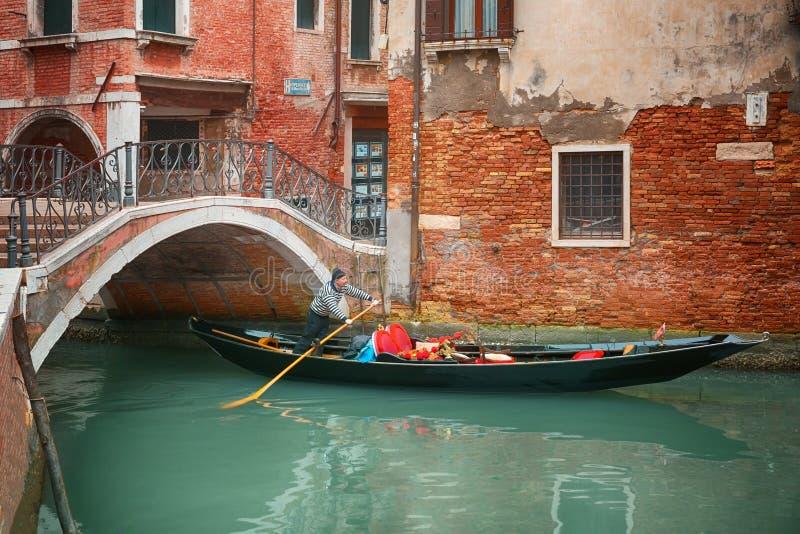 Gondoliere sulla sua gondola sotto il ponte, vela tramite il canale a Venezia, Italia immagine stock