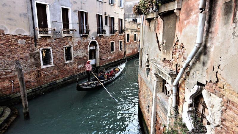 Gondoliere veneziane che galleggiano su una gondola attraverso le acque del canale fra le case di Venezia Italia immagini stock libere da diritti