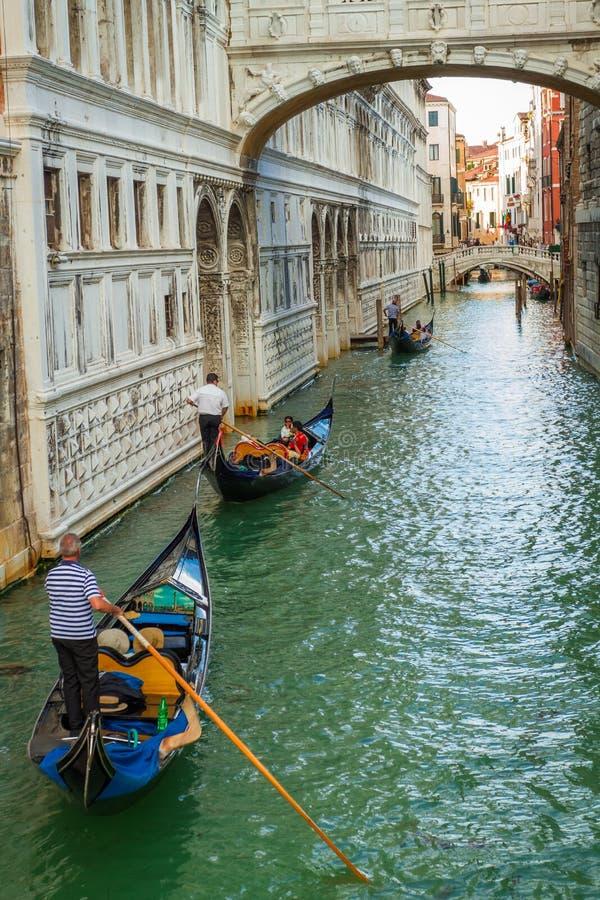 Gondolieri, die auf ein Canal Grande in Venedig schwimmen stockfotografie