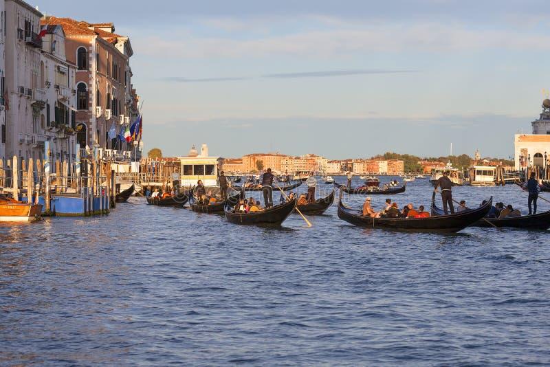 Gondoliers Венеции на гондолах с туристами на грандиозном канале на заходе солнца, Венеции, Италии стоковые фотографии rf