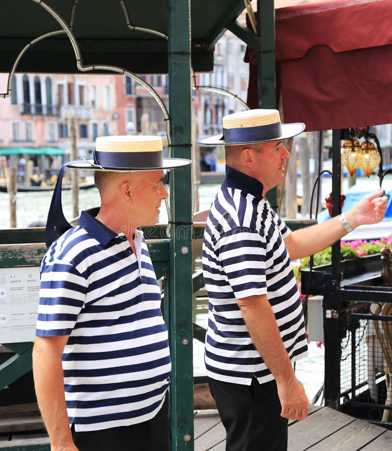 Gondoliers on the pier. VENICE, ITALY - 26 JUNE, 2014: Gondoliers on the pier. The profession of gondolier is controlled by a guild, which issues a limited royalty free stock image