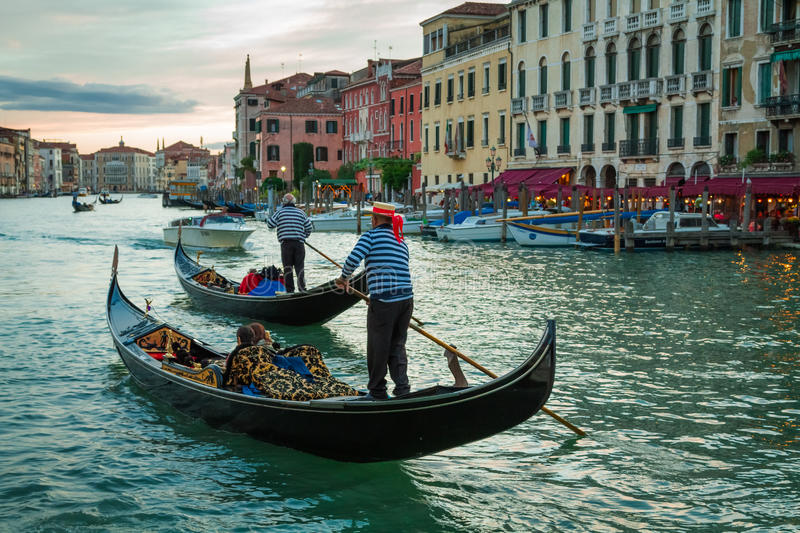 Gondoliers sailing with tourists on the Grand Canal at sunset in royalty free stock photography