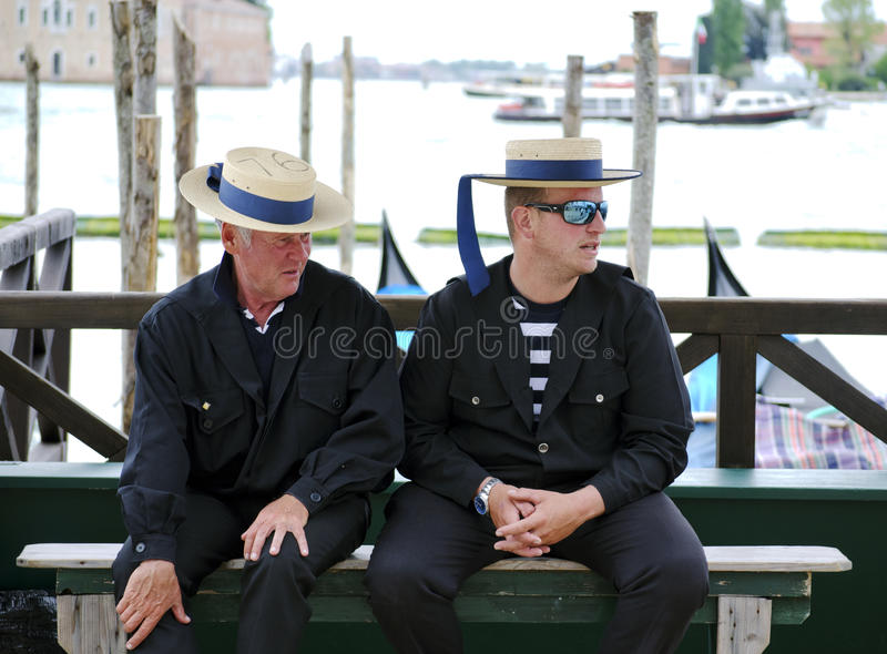 Gondoliers in Venice, Italy. Venice, Italy - April 13, 2014: Two Gondoliers waiting for clients. The profession of gondolier is controlled by a guild, which stock image