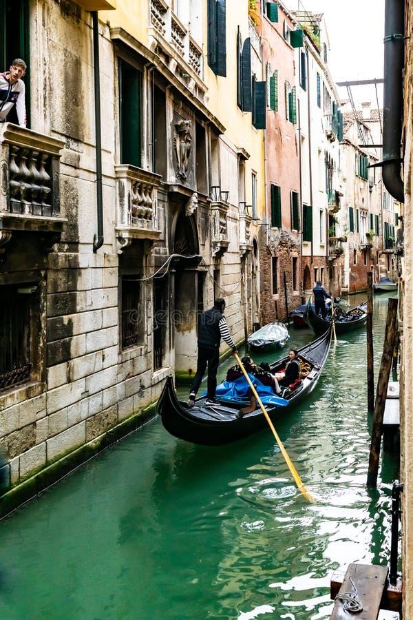 Gondoljärer navigerar gondoler som seglar den smala vattenkanalen med fartyg som förtöjas/anslutas/parkeras bredvid byggnader i V arkivfoton