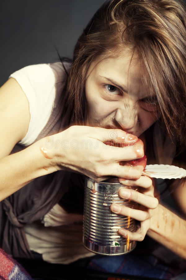 Gone Feral. A young woman enjoying what nourishment she can find in a post apocalyptic world stock photography