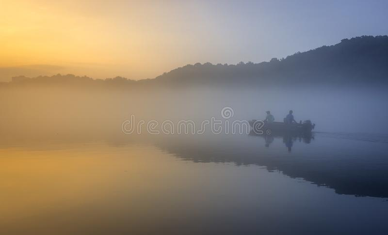 Gone Fishing. A fishing boat in thick fog going upstream on the Chattahoochee river in Georgia royalty free stock image