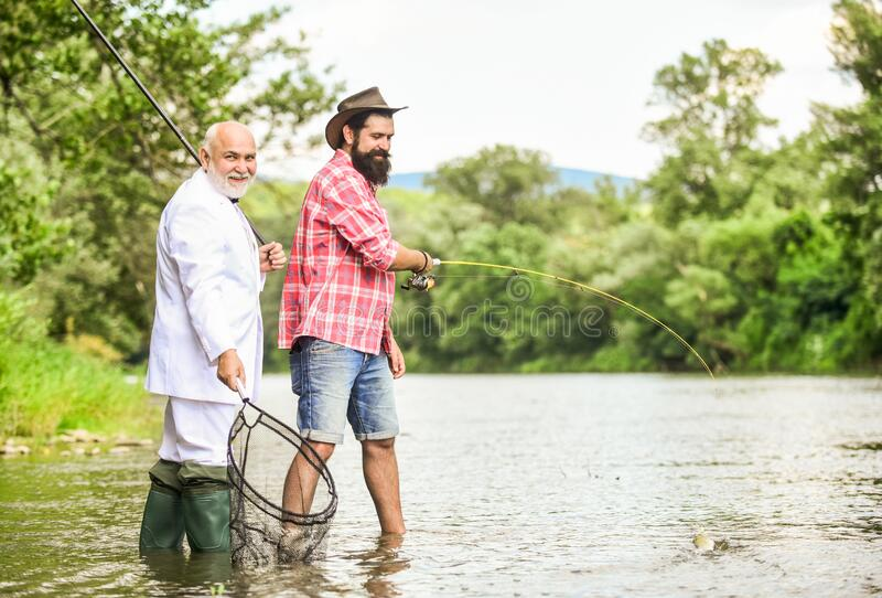 Gone Fishing. hobby of businessman. retirement fishery. retired dad and mature bearded son. friends men with fishing rod. And net. happy fishermen. Good profit royalty free stock image