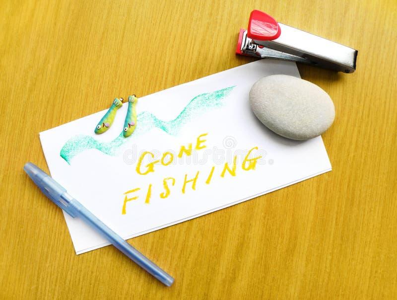 Gone Fishing note on desk stock photo