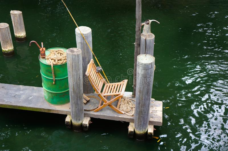 Gone Fishing on the Pier with Pole and Reel. Empty chair and fishing pole await the fisherman`s return. Emerald green river water reflects the sunlight royalty free stock images