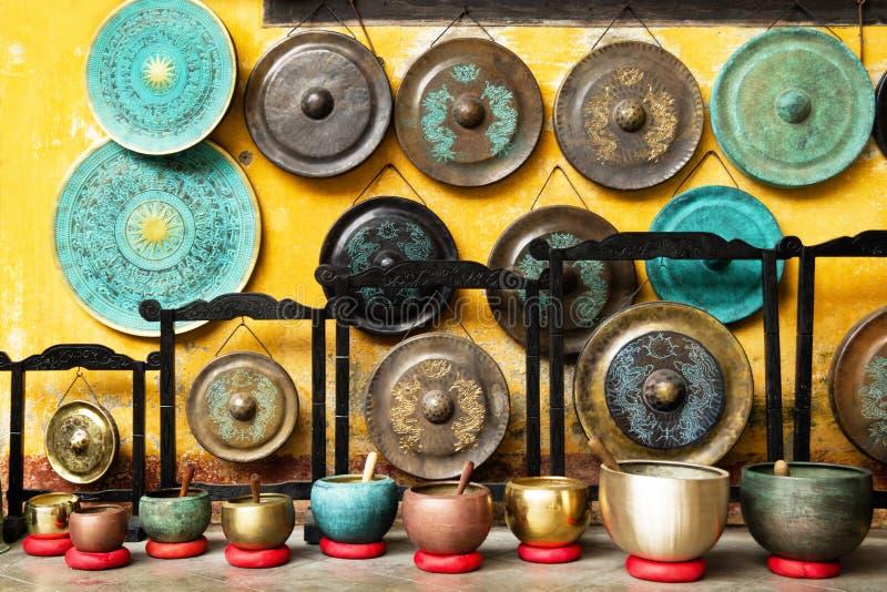 Gongs et cuvettes de chant - instruments de musique asiatiques traditionnels sur un marché en plein air photographie stock libre de droits