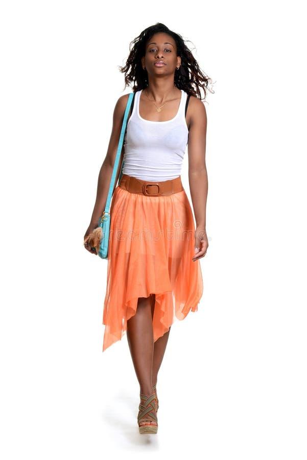 Gonna arancio d'uso di camminata della donna di colore fotografia stock