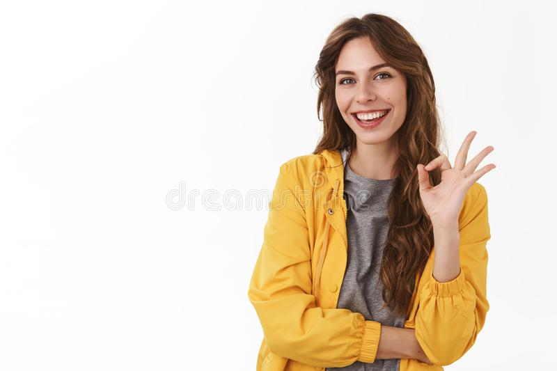 Gonna be okay. Assured carefree relaxed unbothered young cheerful girl show ok agree gesture smiling approval assure royalty free stock photography