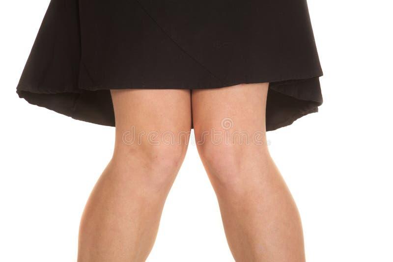 Gonna del nero delle ginocchia della donna fotografia stock