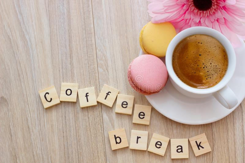 Good afternoon message coffee break concept  white cup of frothy espresso coffee with colourful French macaroons on wooden. Background, space for text royalty free stock images