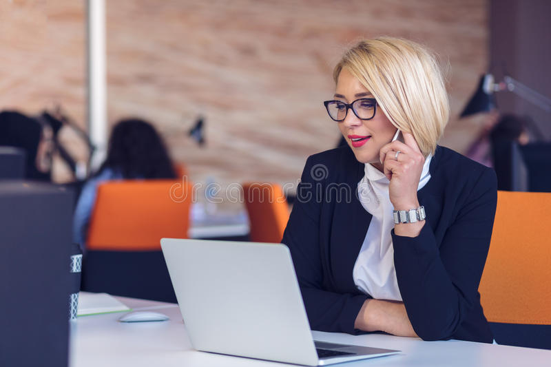 Good business talk. Cheerful young beautiful woman in glasses talking on mobile phone and using laptop stock image