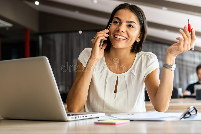 Good business talk. Cheerful young beautiful woman talking on mobile phone and using laptop with smile while sitting at royalty free stock images