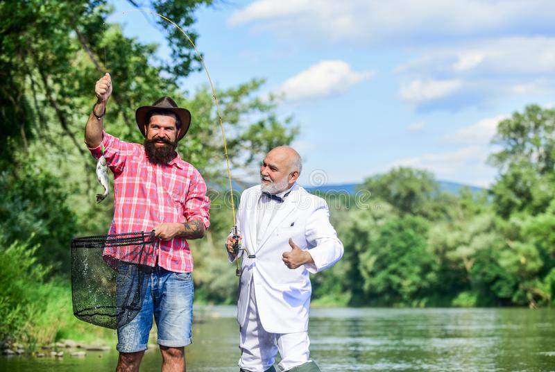 Good catch. Bearded men fishing. Family day. Lucky and skilled. Spinners and tackle. Nice catch. Bait and hook. Hobby royalty free stock photo