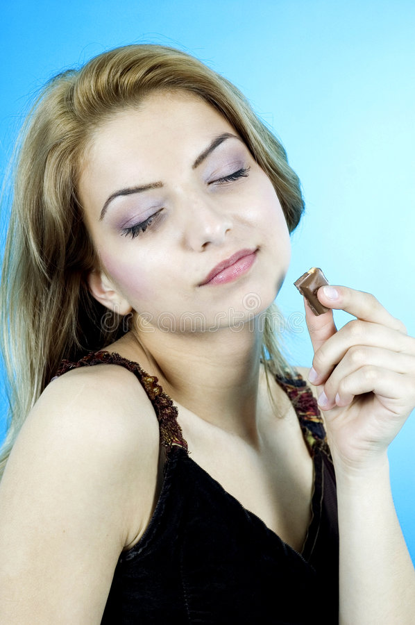 Good Chocolate. Young woman enjoying a piece of chocolate royalty free stock images