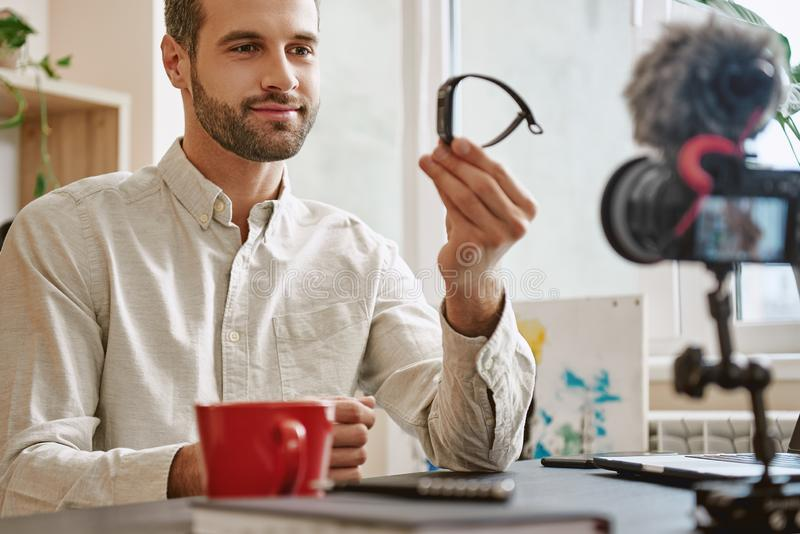 Good choice! Handsome blogger showing smart watch on camera while recording new video for his Youtube Channel stock photos