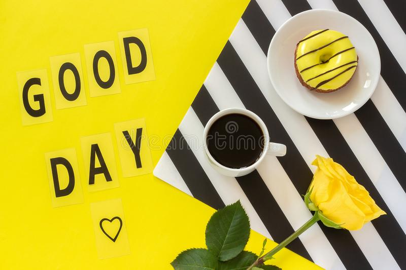 Good day, Coffee, Donut, yellow rose on stylish black and white napkin on yellow background. Minimal style. Concept good day. Flat. Text Good day Coffee, Donut stock image