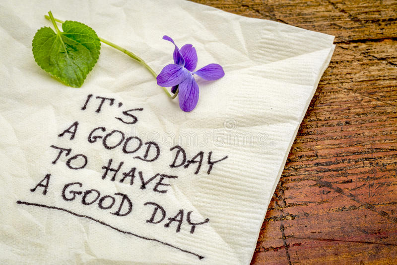 It is a good day. To have a good day - handweiting on a cocktail napkin with a viola flower stock images