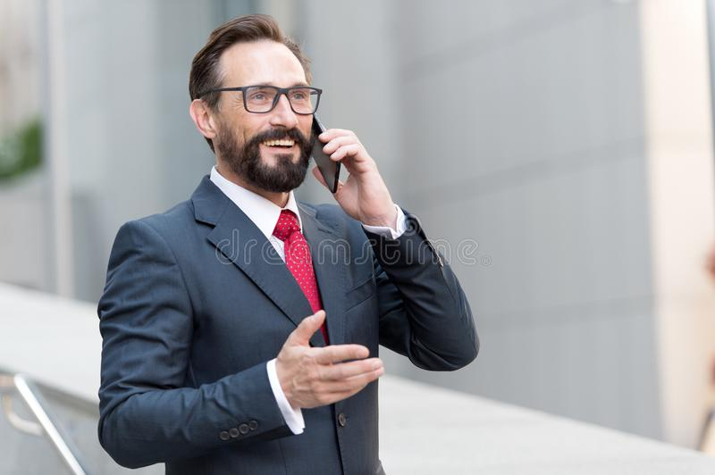 A good deal! Bearded businessman speaks by phone and laughs.View of handsome attractive businessman in glasses using smartphone royalty free stock photo