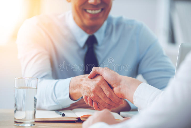 Good deal. Close-up of two business people shaking hands while sitting at the working place royalty free stock image