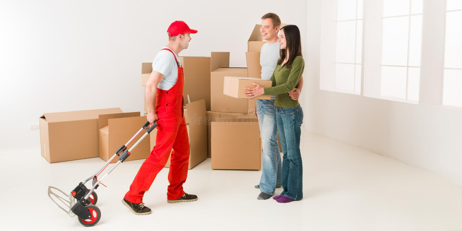 Good delivery service. Couple moving in new home and receiving package from delivery man royalty free stock images