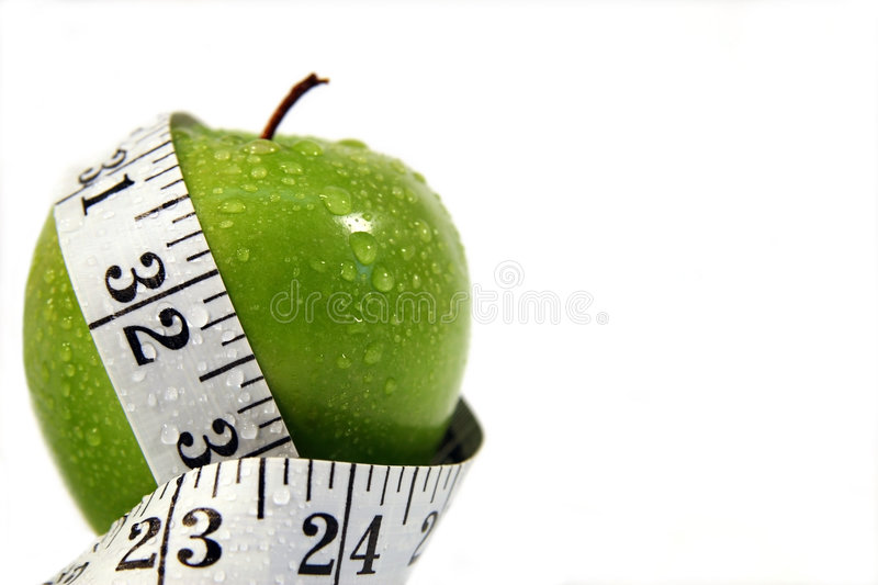Good for the diet. Measurement tape wrapped around green apple/Concept for health, diet royalty free stock image