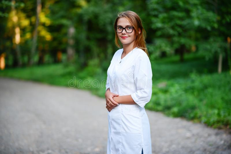 Good doctor. a young girl who is a doctor stands outside, hands stock photography
