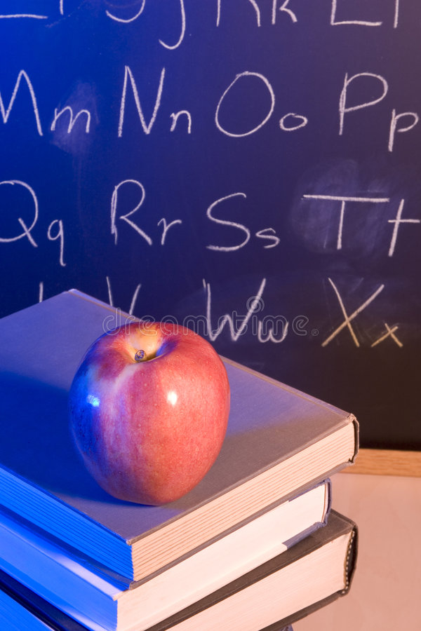A Good Education. Apple on books in front of a chalkboard with the alphabet written on it stock photos