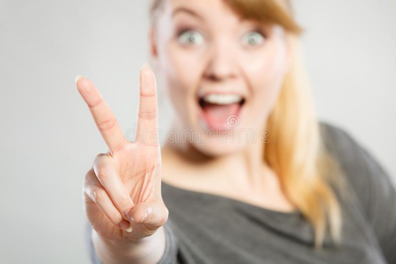 Cheerful female shows victory symbol. Good feeling and positive emotions of win. Cheerful happy female shows two fingers as symbol of victory and won stock photography