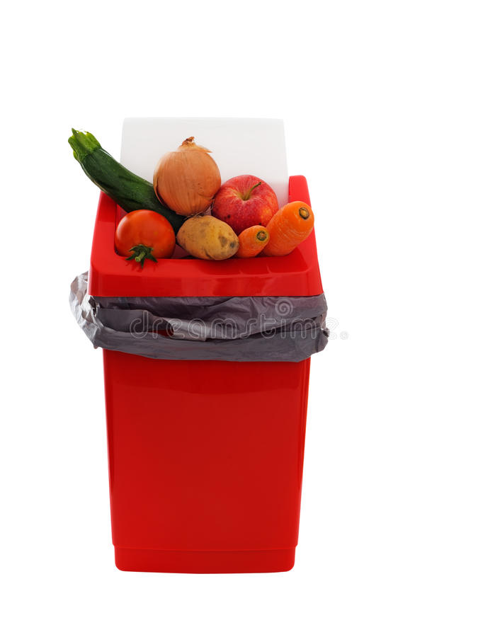 Good food wasted - slightly marked, imperfect vegetables in trash bin, isolated over white background stock photo