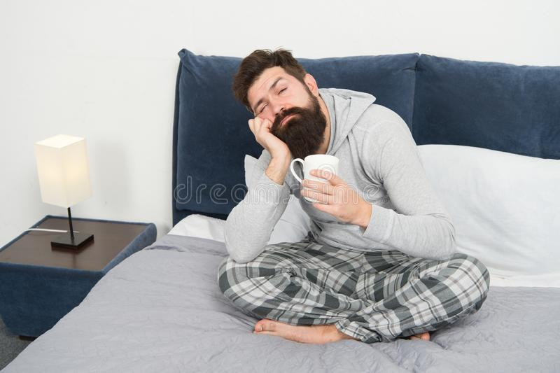 Good gay begins from cup of coffee. Coffee affects body. Man handsome hipster relaxing on bed with coffee cup. Coffee stock photos