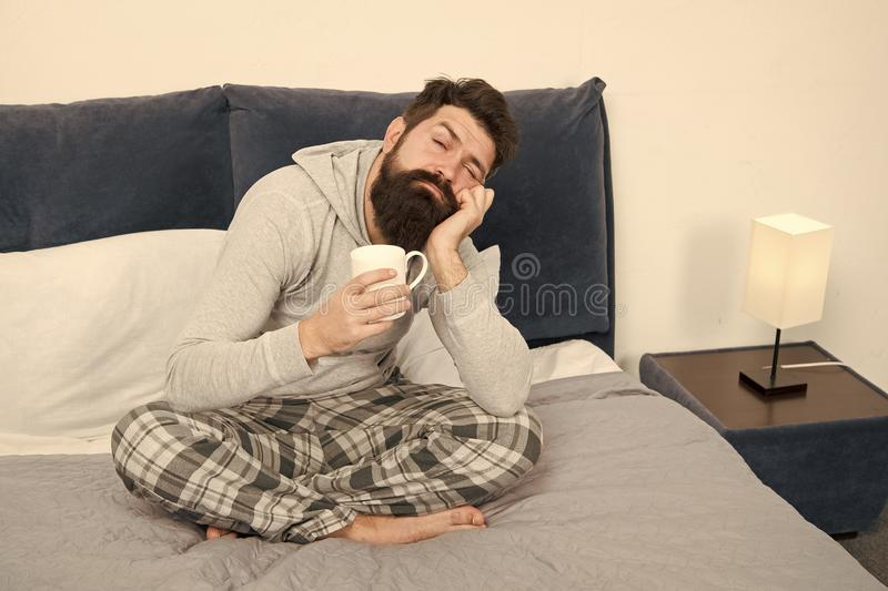 Good gay begins from cup of coffee. Coffee affects body. Man handsome hipster relaxing on bed with coffee cup. Coffee stock photo