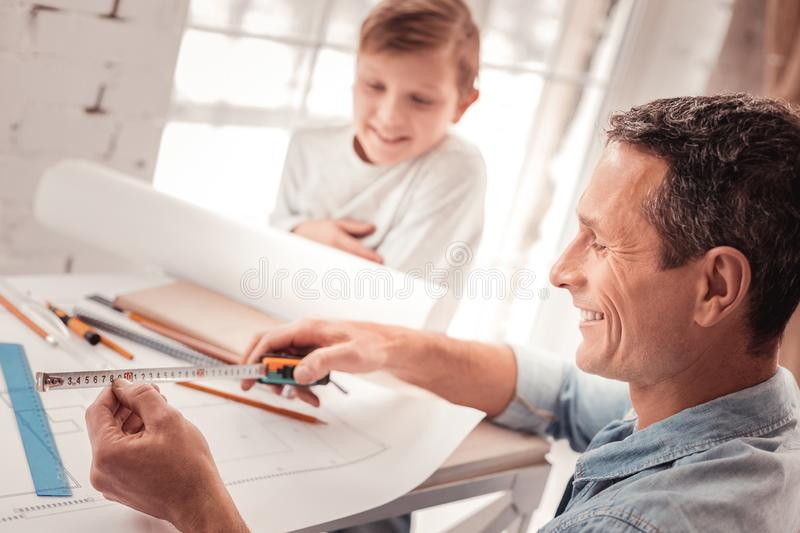 Blonde-haired son listening to his father good in geometry royalty free stock photos