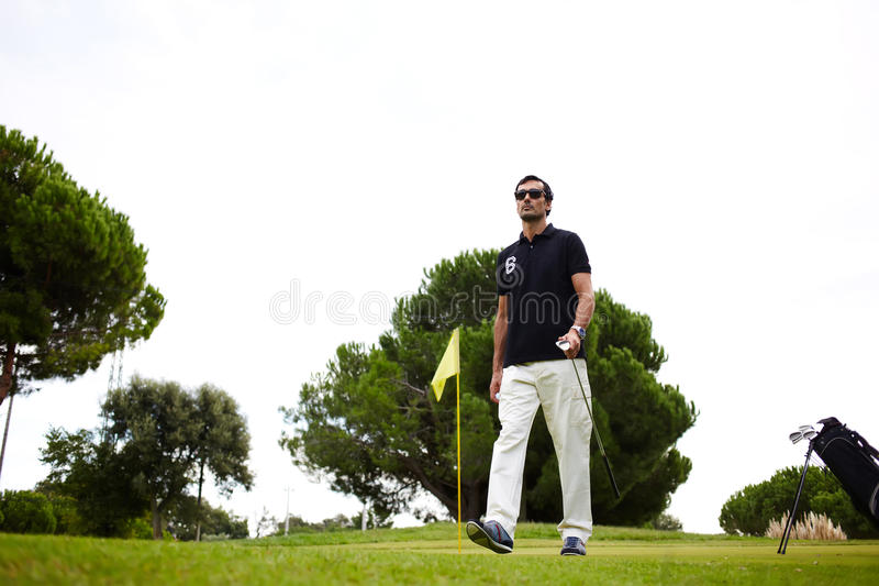 Good golf game at sunny summer day on the course. Full length portrait of professional golf player walking to the next hole in golf course, good golf game at stock image