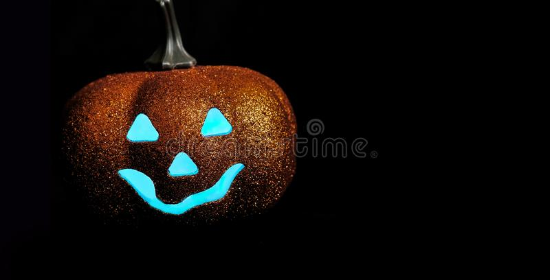 Good Halloween pumpkin on a black background. Free space for text. Blue eyes.Front view stock image