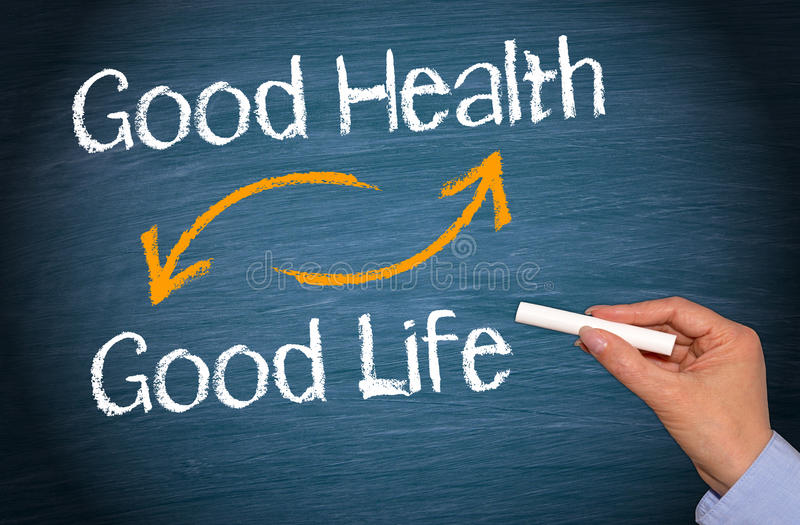 Good Health and Good Life. Female hand with chalk writing text on blue background royalty free stock image