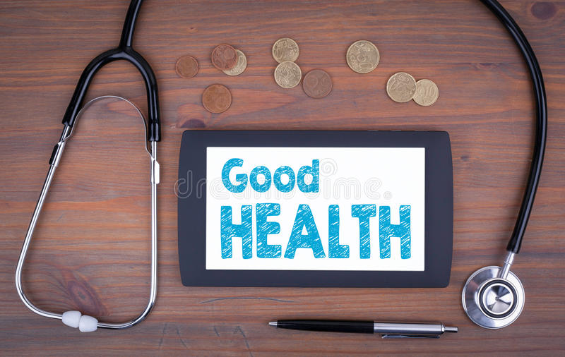 Good Health. Text on tablet device. On a wooden table royalty free stock photo