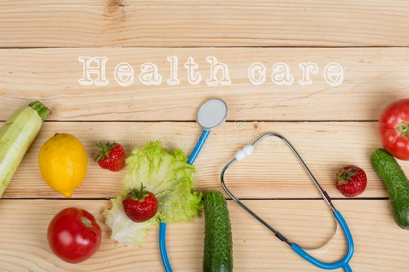 Good healthy and diet concept - text Health Care, stethoscope and vegetables, fruits and berries royalty free stock photo