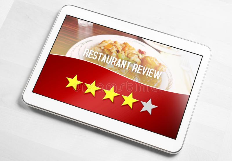 Good hotel review from satisfied and happy customer. And reviewer. Rated four out of five stars. Mobile device on table with an imaginary criticism application stock image