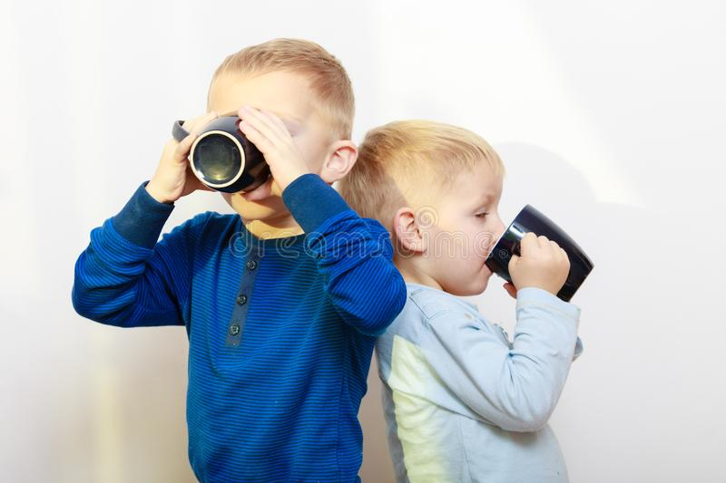 Two boys kids drinking drink from mugs. Good daily human hydration concept. Two boys, thirsty kids drinking drink from black mugs royalty free stock photos