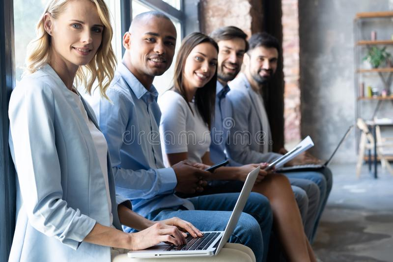 Really good info. Group of young people sitting on conference together and smiling. stock photography