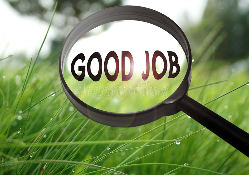 Good job. Magnifying glass with the word good job on grass background. Selective focus stock photos